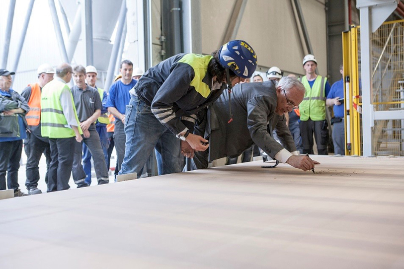 Marco and Giovanni Fantoni sign the first board produced on a 65-meter-long CPS—the longest continuous press that Dieffenbacher has ever built.