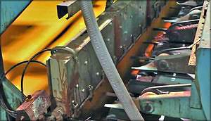 Рис. 14. Прижим шпона перед завесой и клеенаносящая головка (установленная под углом) усовершенствованной линии клеенанесения наливом (производитель – Spar-Tek Industries Inc.)