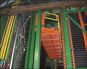 Рис. 18. Платформа обслуживания и загрузочные кронштейны (видны вертикальные поворотные балки с горизонтальными трубами, на концах которых флажки-упоры) пресса Spar-Tek Inc., установленного на ЕФК