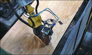 Рис. 21. Робот-манипулятор линии починки фанеры фирмы Pretec и головка манипулятора с фрезой (под кожухом) и наконечником для подачи шпатлевки