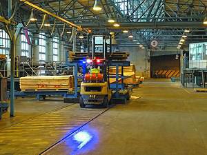 Синий «зайчик» на полу на переднем плане – один из элементов обеспечения безопасности на производстве. Он предупреждает персонал о приближении погрузчика и направлении его движения. При этом скорость движения погрузчиков на предприятии жестко ограничена 5 км/ч