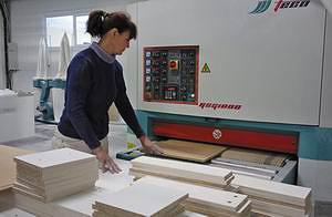 На рельефно-шлифовальном станке V-Hold QSG 1000 детали из MDF проходят обработку перед грунтовкой